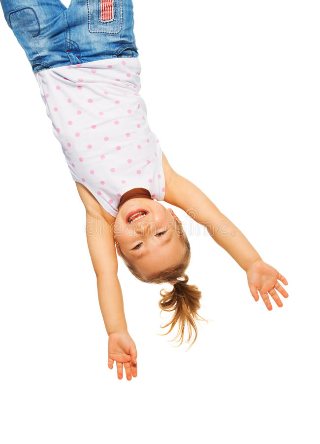 Little girl hanging upside down royalty free stock images