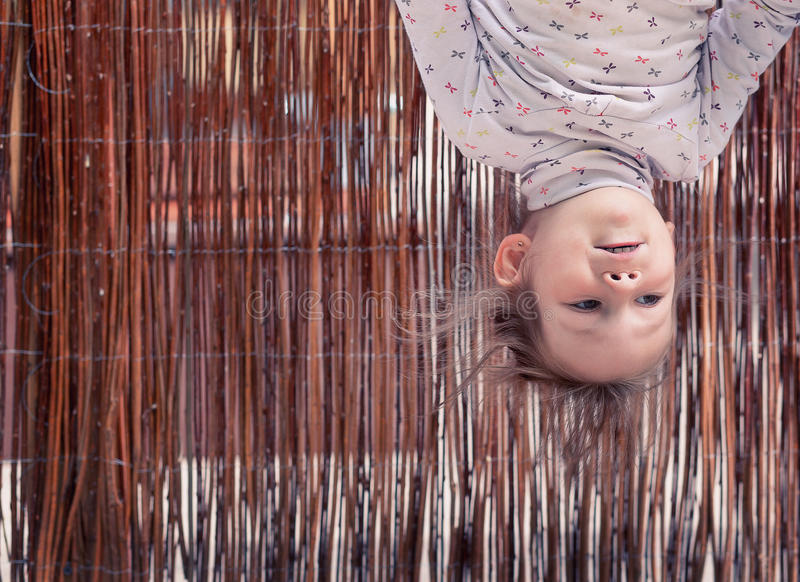 Little girl hanging upside down royalty free stock photo