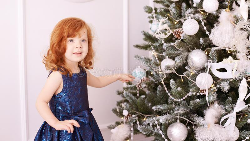 Little girl. Happy child. Blue dress. Christmas decorations royalty free stock images
