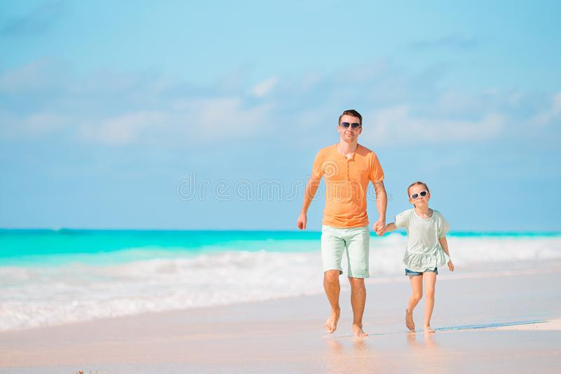 Little girl and happy dad having fun during beach vacation royalty free stock photos