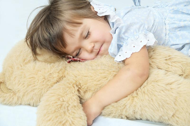 Little girl happy sleeping smiley with Teddy bear stock images
