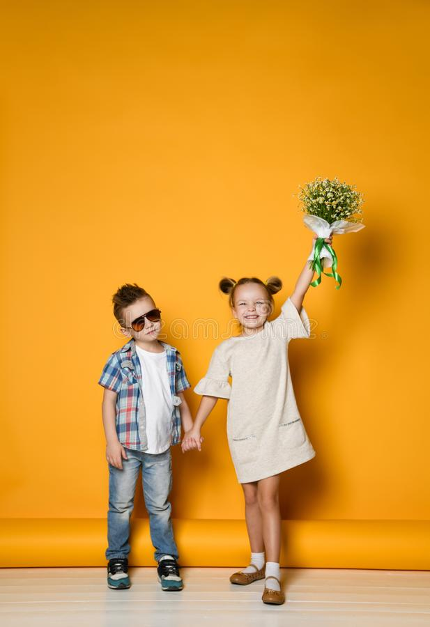 Young happy caucasian boy gives a flowers to his girlfriend isolated over yellow background. stock image
