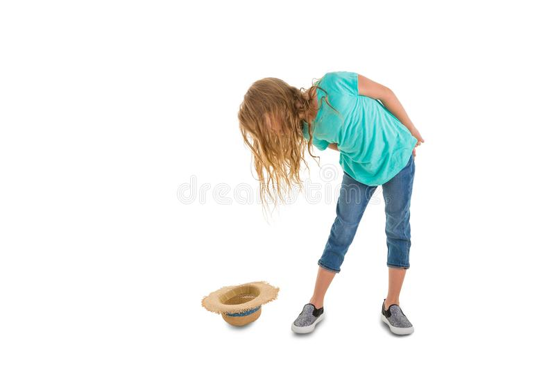 Little girl has dropped a straw hat on the ground stock photography