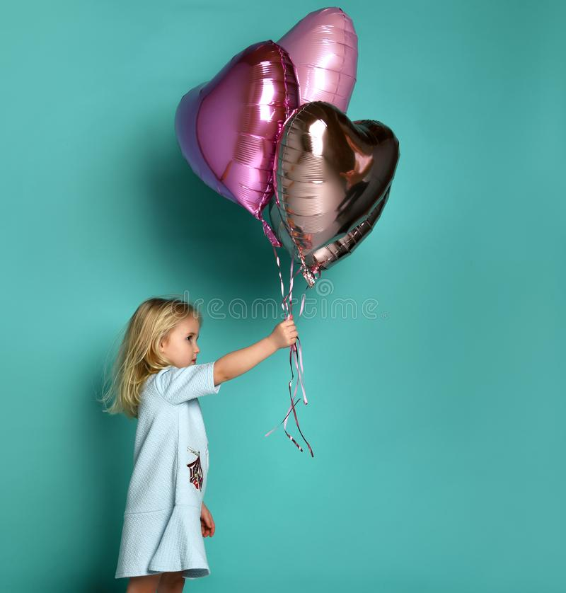 Little girl has fun with a bunch of pink air balloons in the shape of her heart stock images