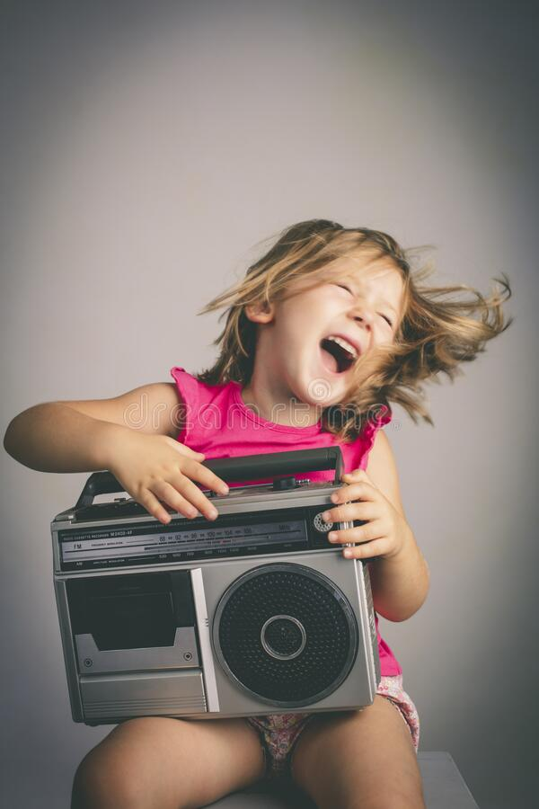 Little girl has fun listening to music royalty free stock photography