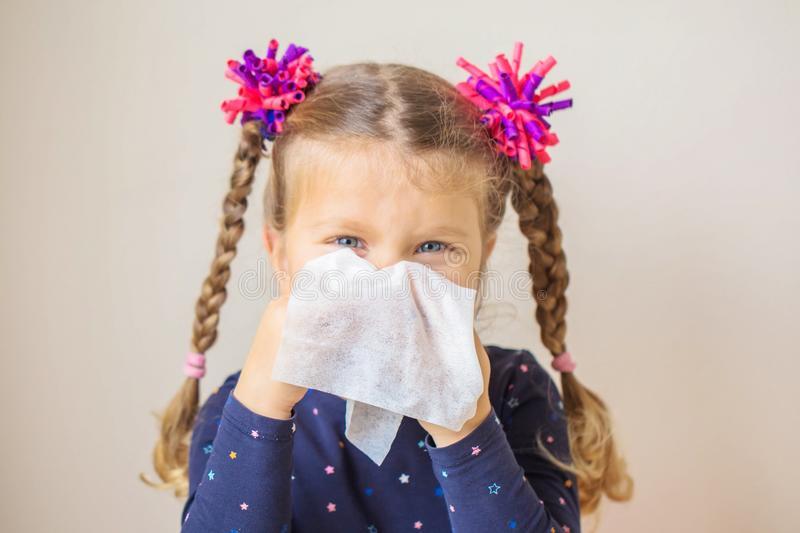 The little girl has a runny nose and blows her nose into a paper. Handkerchief. Children`s cold, selective focus on a handkerchief. Acute respiratory viral royalty free stock images