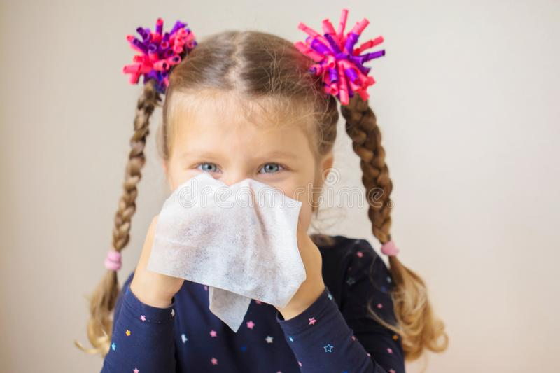 The little girl has runny nose and blowsnose into handkerchief. The little girl has a runny nose and blows her nose into a paper handkerchief. Children`s cold royalty free stock photos