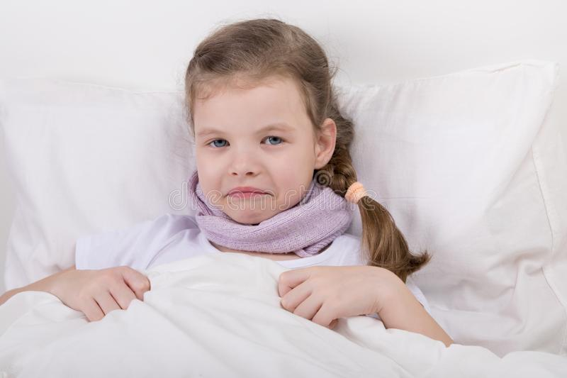 Little girl has a sore throat, she warms him, lying in bed stock photo