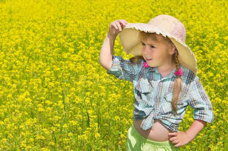 The little girl in the hat among the blossoming of stock image