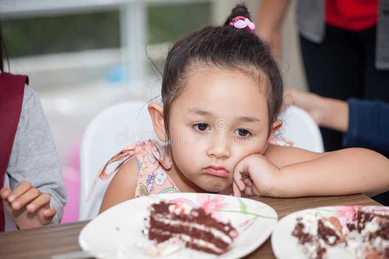 Little girl with hat bored eating birthday cake royalty free stock photo