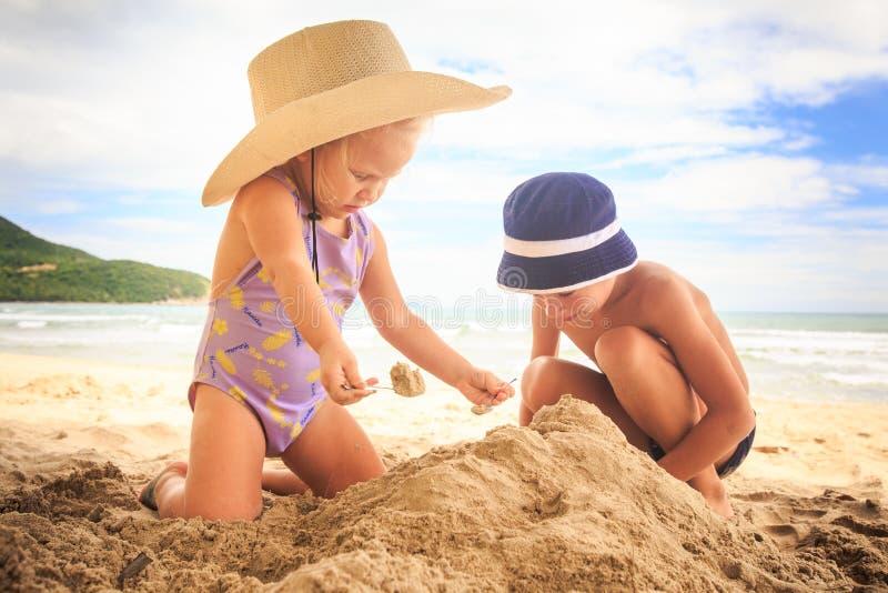 Little Girl in Hat Boy Spread on Sand Heap on Beach by Surf stock image