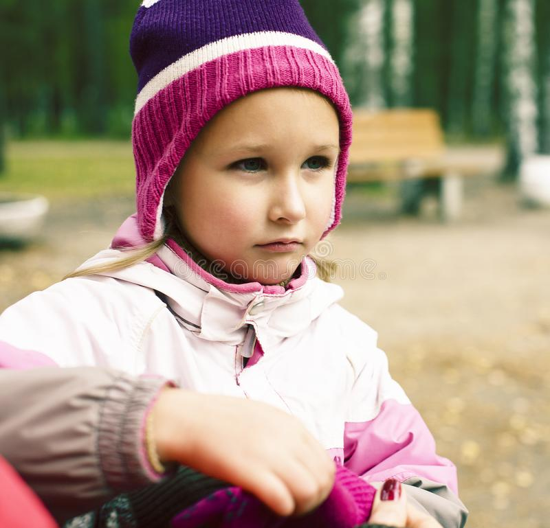 Little girl in hat dressing up gloves with mothers help in park outside stock photography