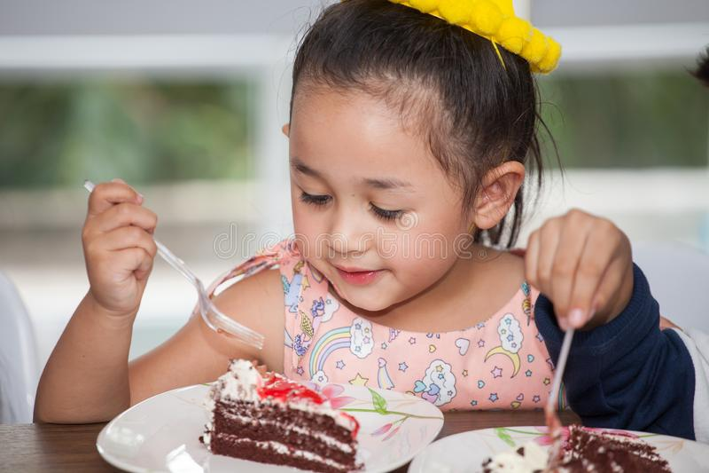 Little girl with hat eating birthday cake stock photo