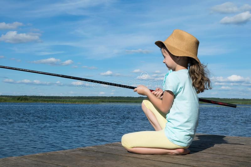 Little girl with a hat is fishing on a lake on a sunny day stock image