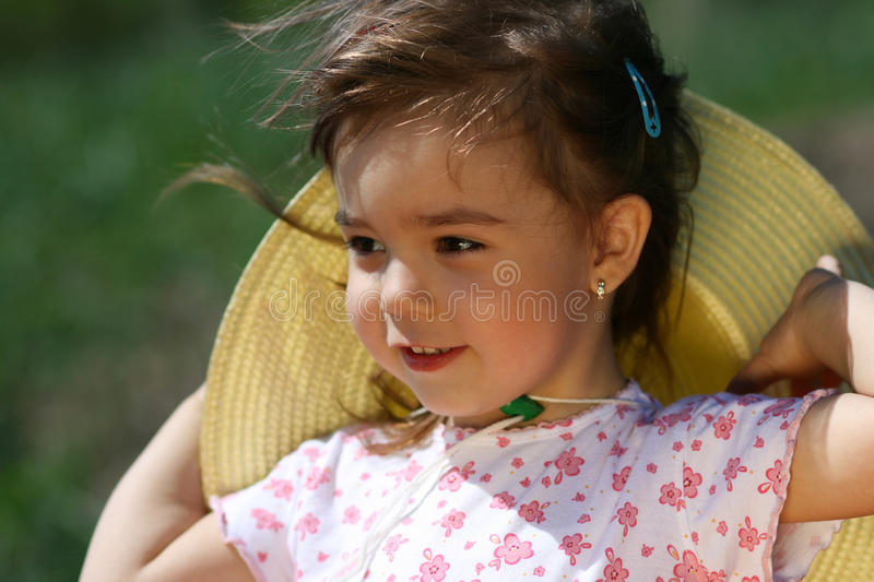 Little girl with hat and hair in wind royalty free stock images