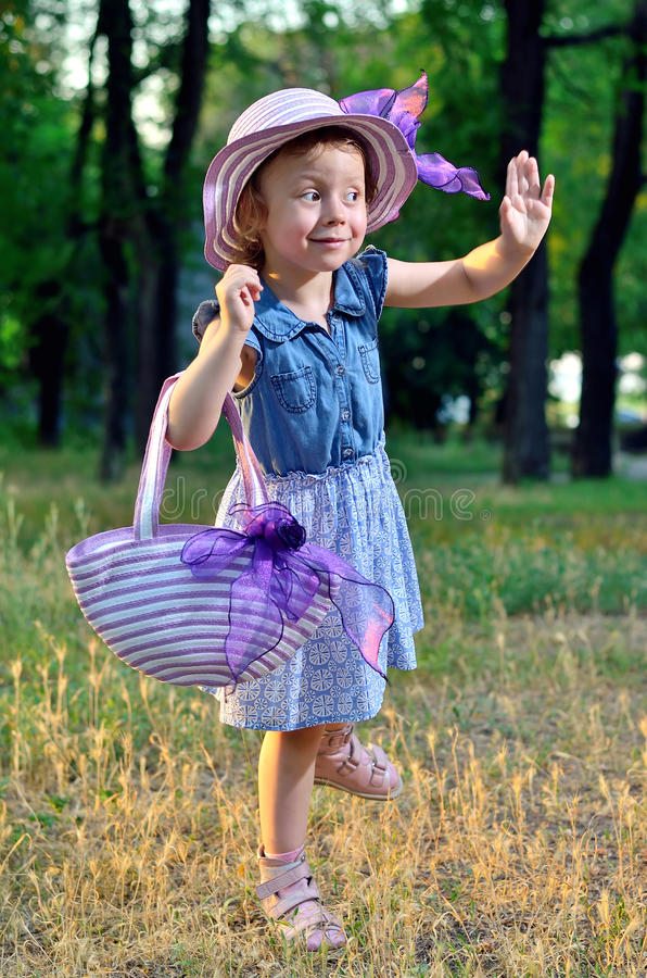 Little girl in a hat and handbag in nature. royalty free stock images