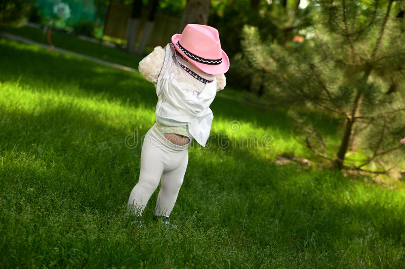 A little girl in a hat is hiding in her dress stock photos