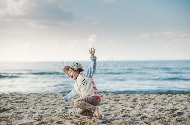 Little girl with a hat jumping and running on the royalty free stock photo