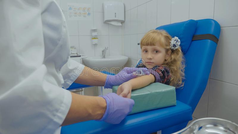 Nurse is taking blood sample from a vein in the arm of little girl stock images