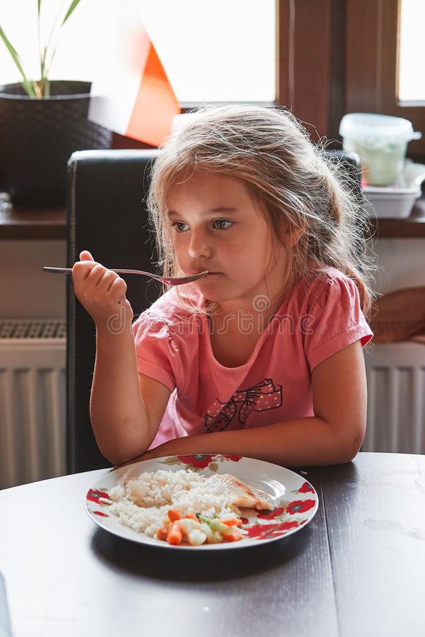Little girl having a dinner at home. Meal on a plate on table, kid holding a fork royalty free stock image