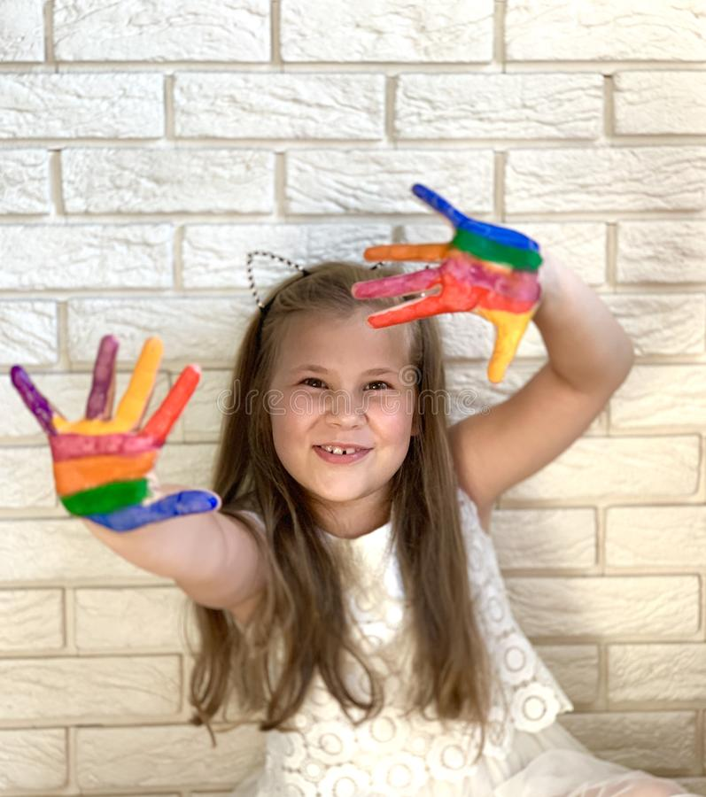 A little girl is having fun, colored paint on her hands. stock photos