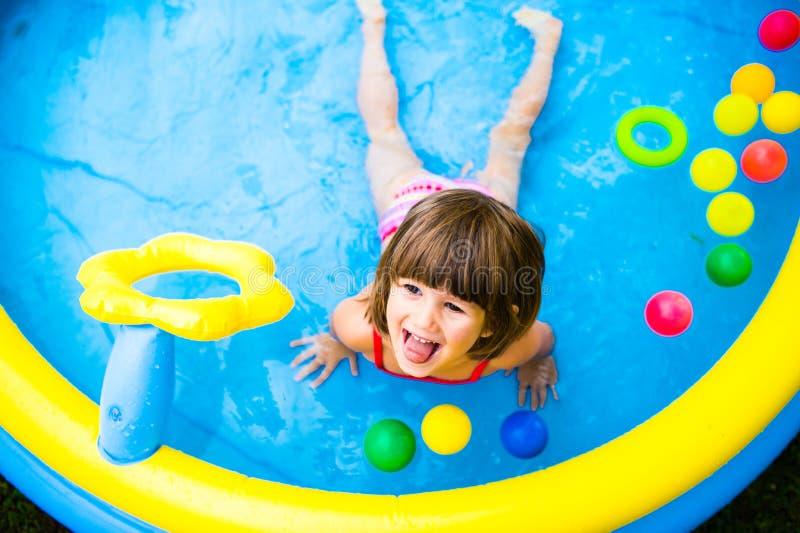 Little girl having fun in the garden swimming pool. stock image