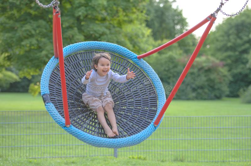 Little girl having fun in one rounded swing stock photos