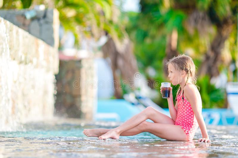 Little girl in outdoor swimming pool enjoy her vacation with tasty drink. Little girl having fun in outdoor swimming pool stock photo