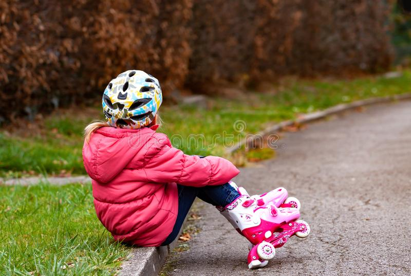 Little girl having fun with roller skates at a park stock images