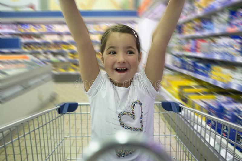Little girl having fun at supermarket. She is outstretching arms royalty free stock photo