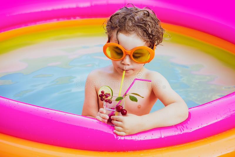 Little girl having fun in swimming-pool. Maldives or Miami beach water. Cute kid relaxing on swimming pool. Child having royalty free stock images