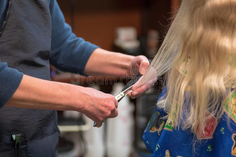Little girl having hair cut at the salon royalty free stock photography