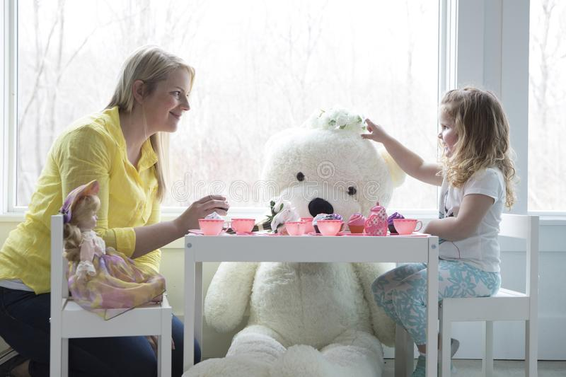 A mom and toddler having a tea party. A little girl having a pretend tea party with her mom.Her giant teddy bear looks on stock photo