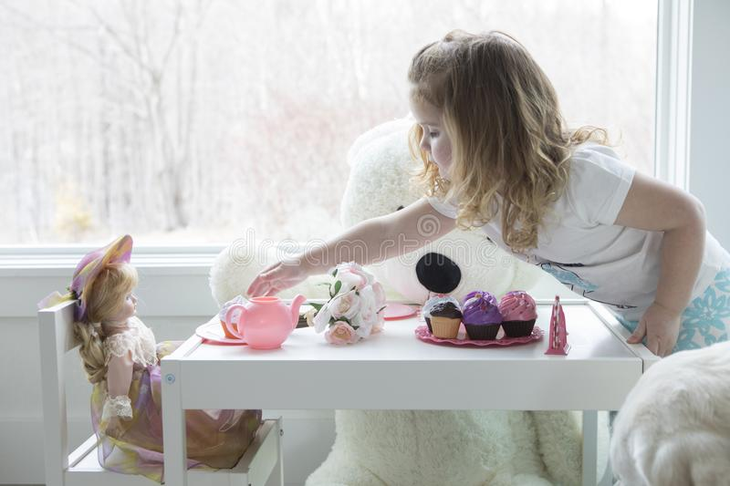 A little girl playing tea party. A little girl having a pretend tea party with her toys and dolls royalty free stock photo