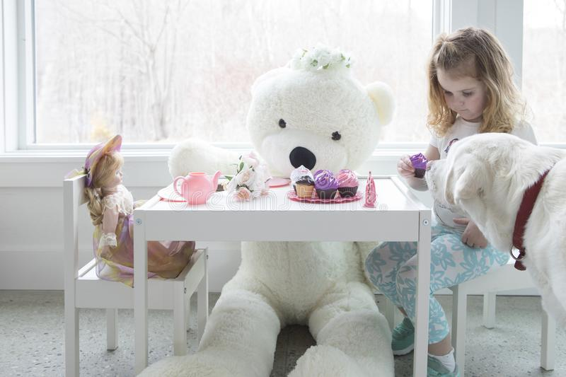 A little girl having a tea party with her toys,. A little girl having a pretend tea party with her dog and toys stock images