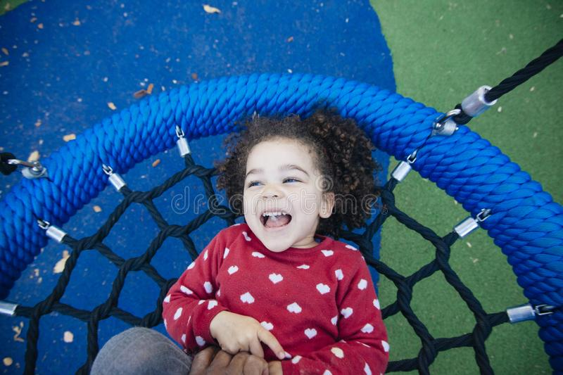 Little girl having a tickle attack at the park royalty free stock photography