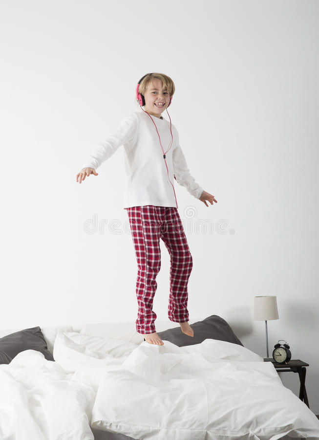 Little girl with Headphones jumping in bed stock photo