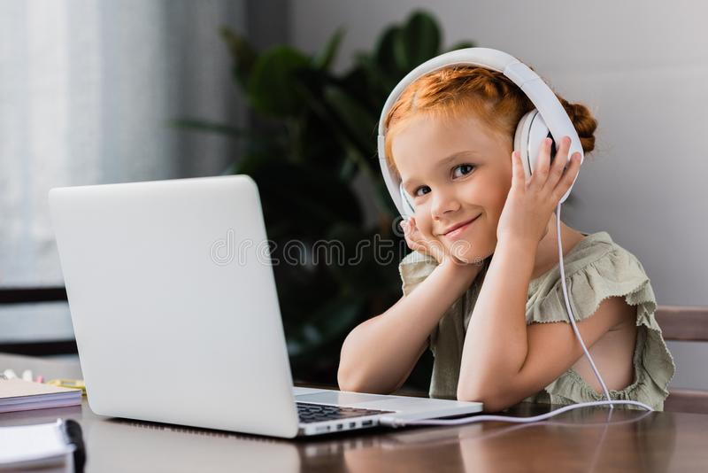 Little girl with headphones and laptop stock images