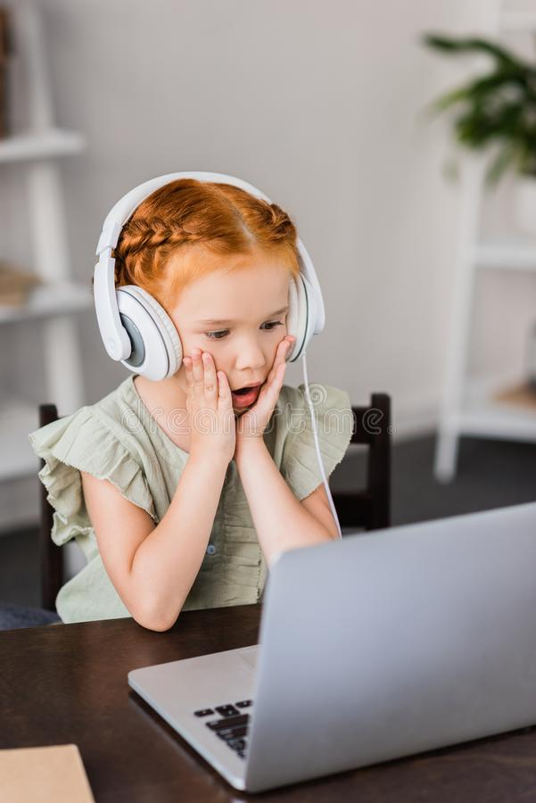 Little girl with headphones and laptop royalty free stock images