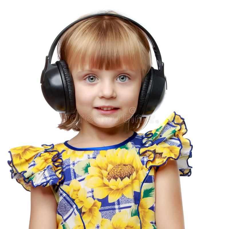 A little girl with headphones listening to music. stock photo