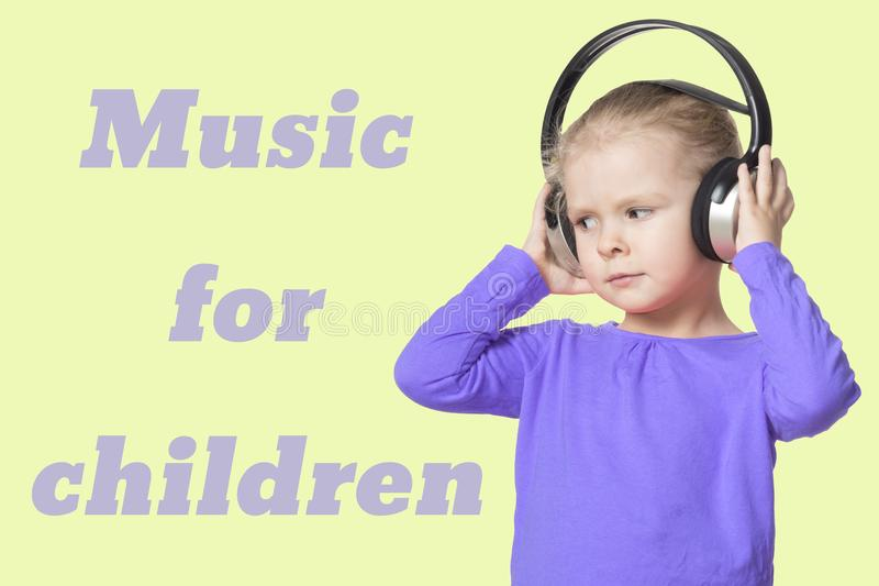 A little girl with headphones listening to music. Isolate. The inscription music for children . Beautiful card royalty free stock photo
