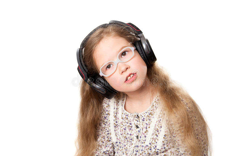 Little girl in headphones listens to music stock photo