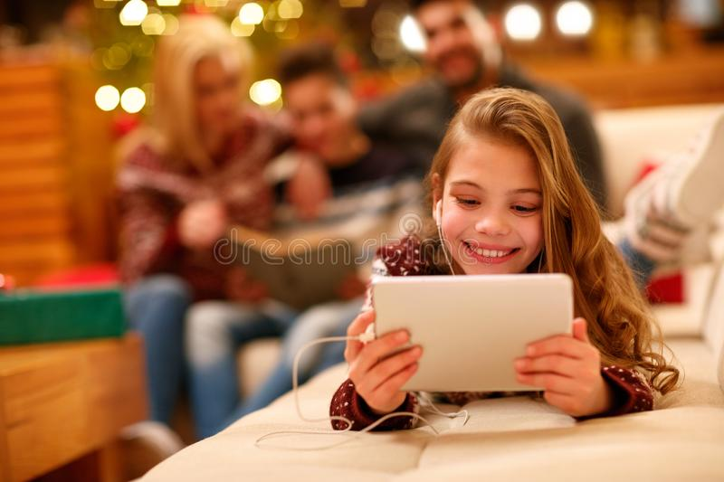 little girl with headphones lying and using a tablet on Christmas day. stock photo