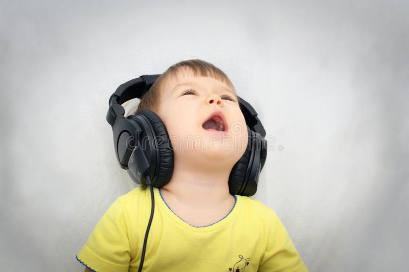 Little girl with headphones singing song. Loudly stock photos