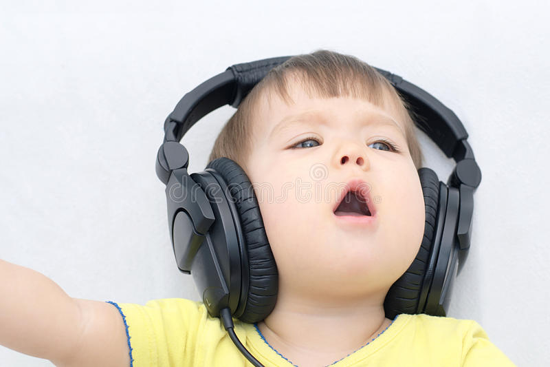 Little girl with headphones singing song. Loudly stock image