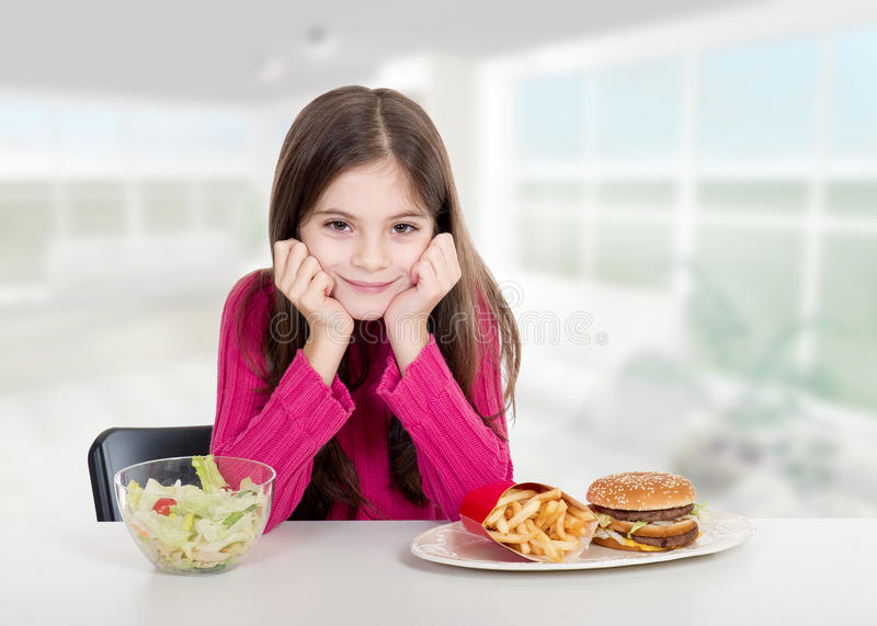 Little girl with healthy and unhealthy food royalty free stock photo