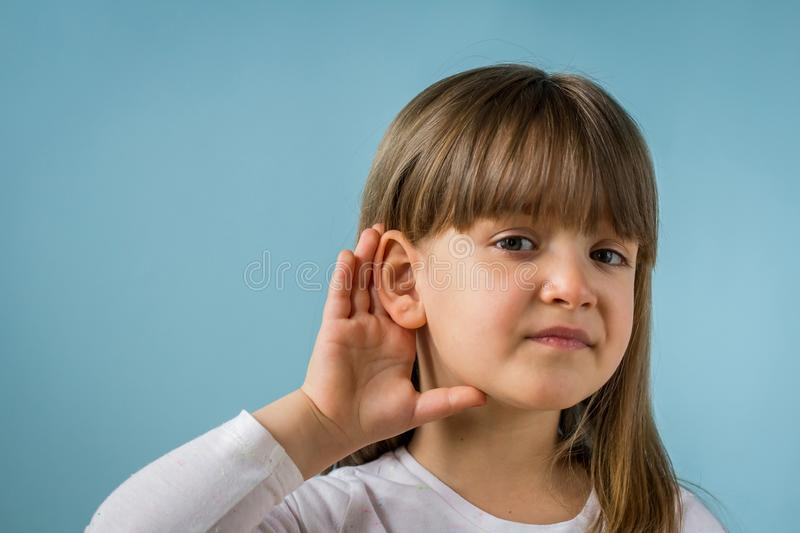 Little girl with hearing problem on light blue background. Close up, copy space. Child with hearing problem on blue background. Hearing loss, symptoms and royalty free stock photo