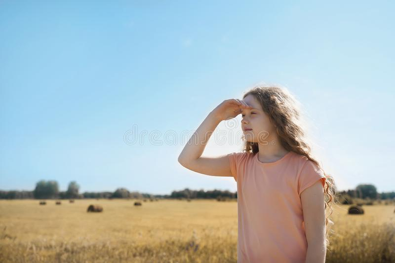 Little girl held out her hand and looks into the distance royalty free stock photo