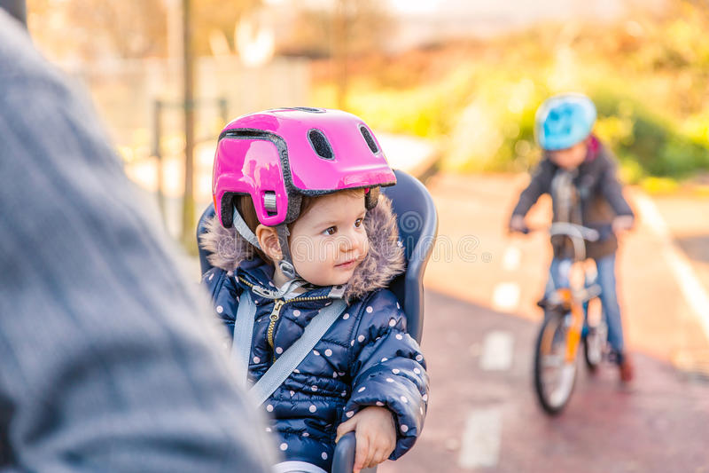 Little girl with helmet on head sitting in bike stock image