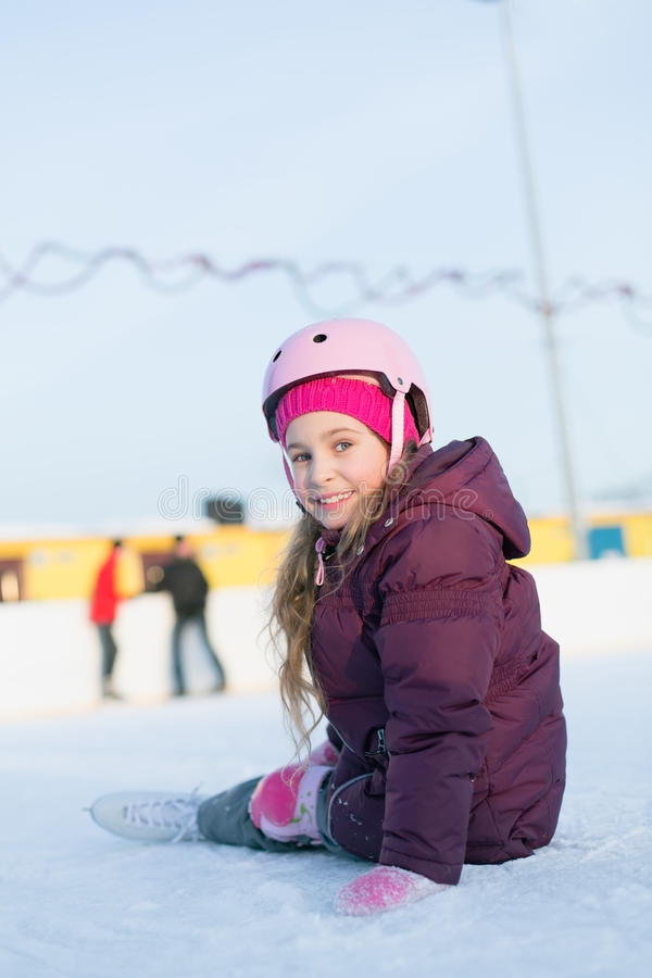 Little girl in a helmet and knee pads sitting at the rink. Smiling little girl in a helmet and knee pads sitting at the rink in winter royalty free stock photography